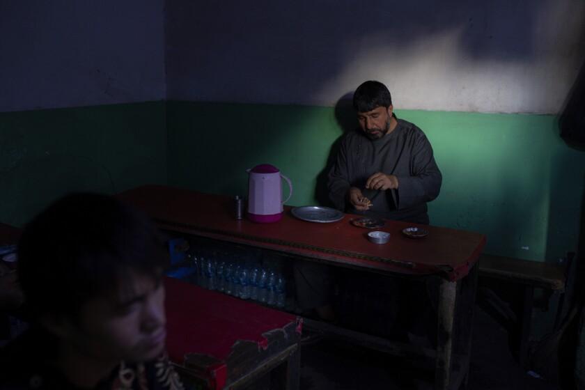 An Afghan eats lunch a market restaurant in Kabul, Afghanistan, Tuesday, Oct. 12, 2021. (AP Photo/Ahmad Halabisaz)