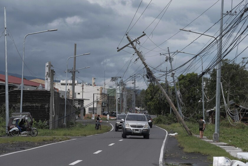 Vehicles pass by toppled electrical poles as Typhoon Kammuri slams Legazpi city.