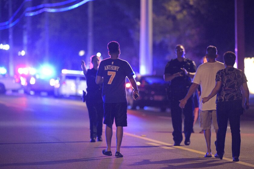 In this photo taken June 12, 2016, Orlando Police officers direct family members away from a shooting involving multiple fatalities at the Pulse Orlando nightclub in Orlando, Fla. The Justice Department said Friday, July 15, 2016, that it will review the Orlando Police Department's response to the attack last month at a gay nightclub. (AP Photo/Phelan M. Ebenhack)