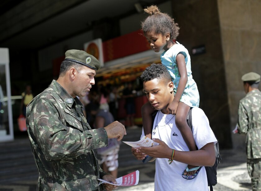 An army soldier explain how to combat the Aedes aegypti mosquito that spreads the Zika virus, at the Central station, in Rio de Janeiro, Brazil, Saturday, Feb. 13, 2016. More than 200,000 army, navy and air force troops are fanning out across Brazil to show people how to eliminate the Aedes aegypti