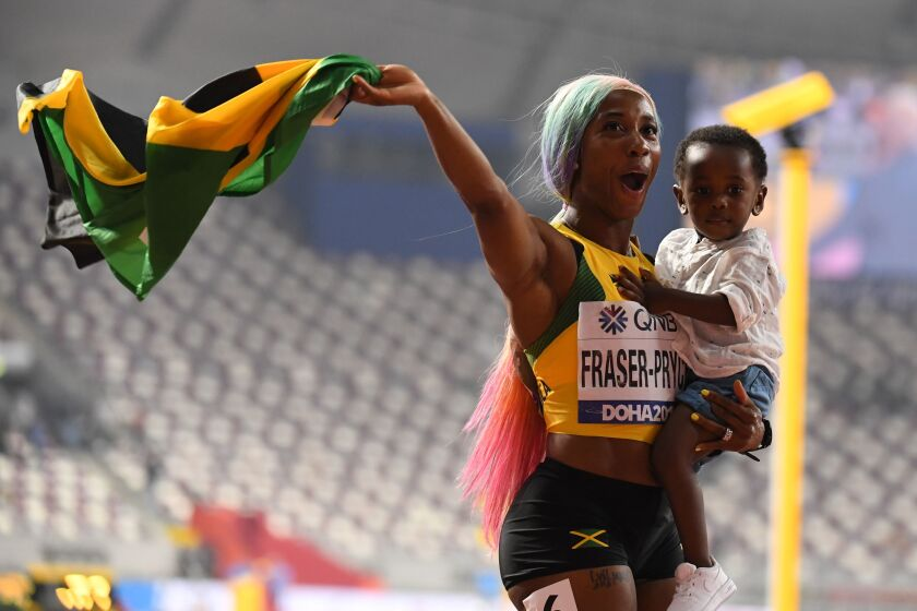 Jamaica's Shelly-Ann Fraser-Pryce celebrates with her son after winning the women's 100-meter final Sunday.