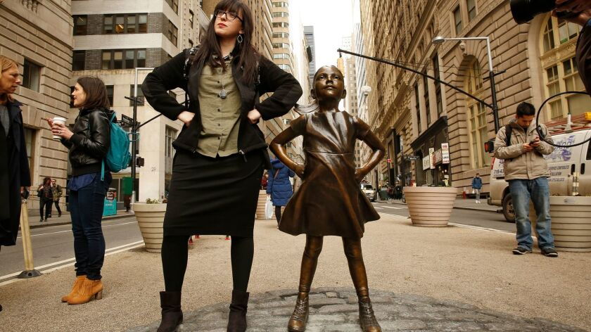 """New York: Layah Shagalow beside a new bronze statue, """"Fearless Girl,"""" that stands near Wall Street's famed """"Charging Bull"""" on International Women's Day."""