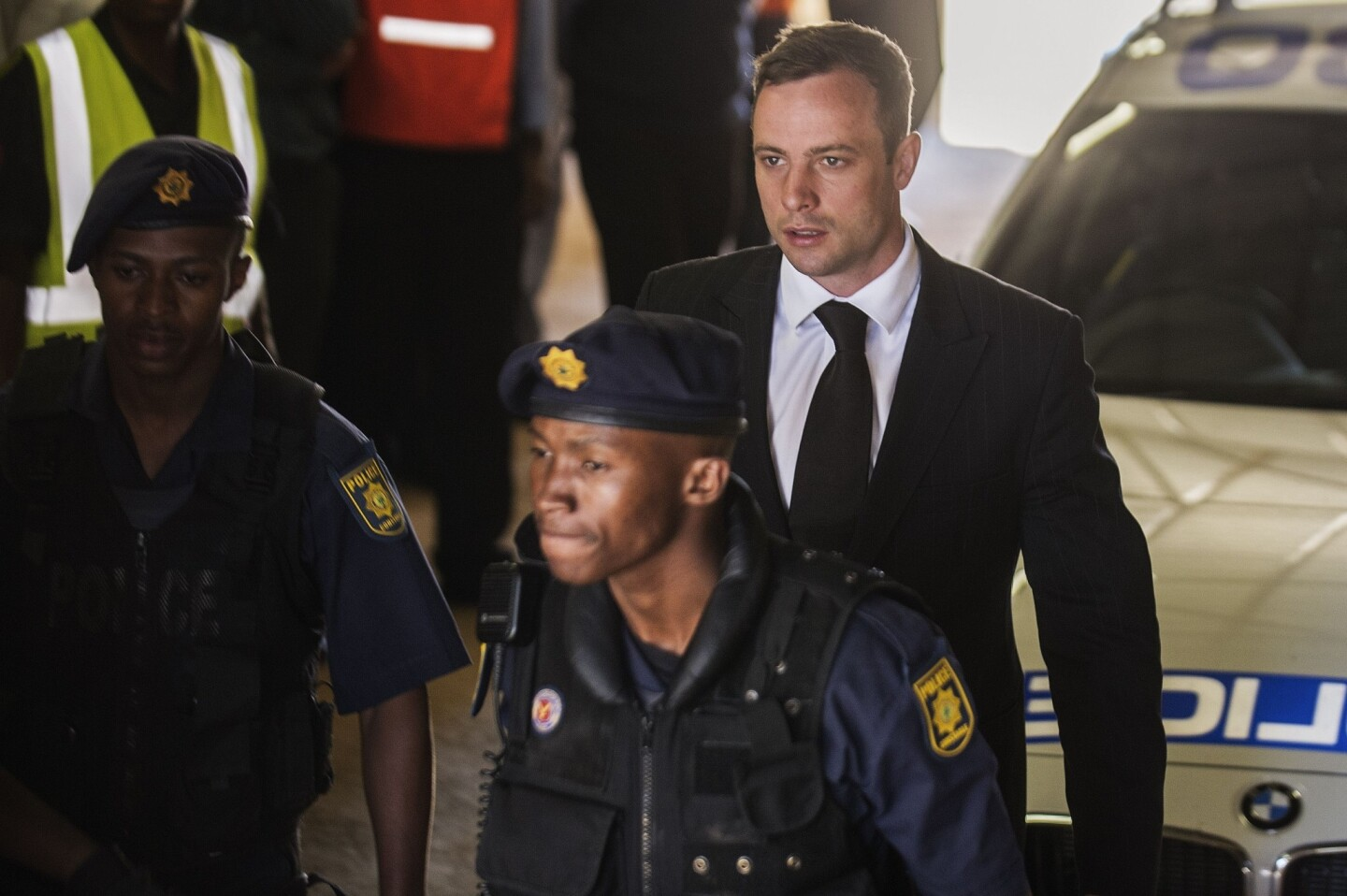Oscar Pistorius is escorted to a police vehicle to be transported to prison after being sentenced to five years for the negligent killing of his girlfriend Reeva Steenkamp in 2013.
