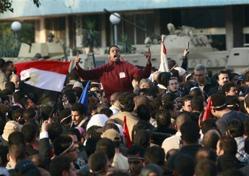 Egyptian anti-government protesters shout in front of the Egyptian television headquarters in Cairo, Egypt, Friday, Feb. 11, 2011. Egypt's military seemed to throw its weight Friday behind President Hosni Mubarak's plan to stay in office until September elections while protesters massed near the pr