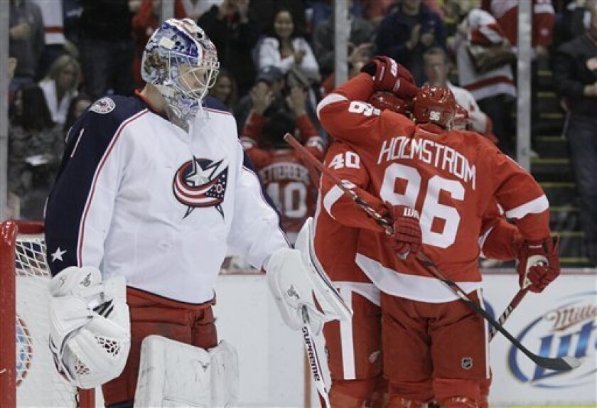 The Detroit Red Wings congratulate teammate Detroit Red Wings left wing Tomas Holmstrom (96) next to Columbus Blue Jackets goalie Steve Mason (1) after his during the first period of an NHL hockey game in Detroit, Monday, March 26, 2012. (AP Photo/Carlos Osorio)