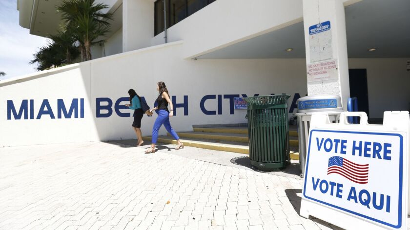 Pedestrians walk past a sign for a polling station at Miami Beach City Hall, Monday, Aug. 13, 2018,