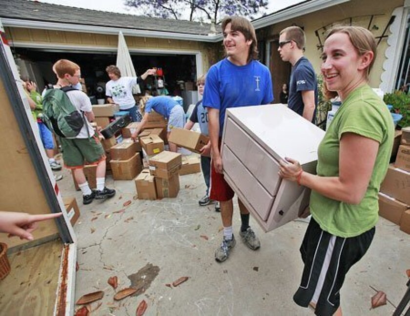 Rosalie Hughes (right), 21, and brother Samuel, 17, loaded furniture into a storage container Thursday at 