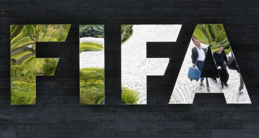 Dos personas aparecen reflejadas en el logotipo de la FIFA en la sede del organjsmo el miércoles, 27 de mayo de 2015, en Zúrich, Suiza. Las autoridades estadounidenses y suizas investigan a dirigentes de la FIFA por corrupción.