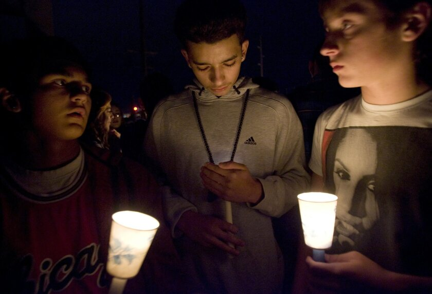 FILE - In this Thursday, Nov. 29, 2012 file photo, mourners hold candles as they stand on a pedestrian bridge during a vigil for a junior high school student who died in an apparent suicide on a pedestrian bridge near Bennion Junior High School in Taylorsville, Utah. A report released by the Centers for Disease Prevention and Control on Wednesday, Oct. 8, 2014 says although Americans are living longer than ever before - rates in 2012 are falling for most of the leading causes of death, with one exception of the still-climbing suicide rate which reached its highest point in 25 years. (AP Photo/The Salt Lake Tribune, Kim Raff)