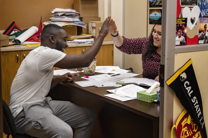 LOS ANGELES, CA - MARCH 7, 2019: Senior Damion Lester, Jr. gets a high-five from college counselor