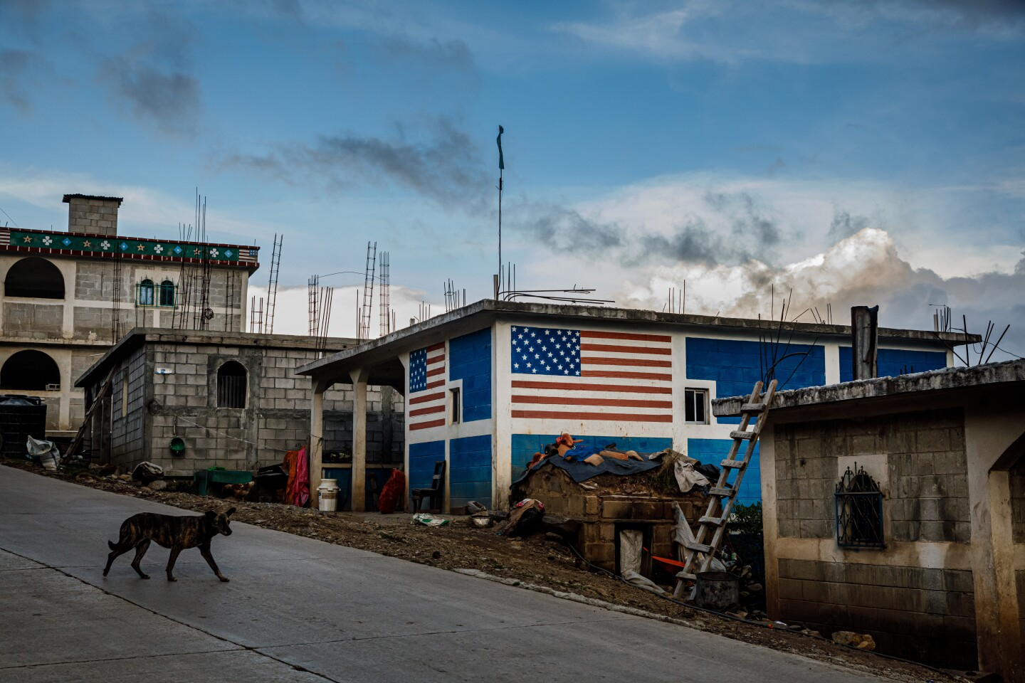 TODOS SANTOS CUCHUMAT?N, DEPARTMENT OF HUEHUETENANGO -- TUESDAY, JUNE 25, 2019: A dog walks by a home decorated with the American flag painted on its walls, near Todos Santos Cuchumat?n, Guatemala, on June 25, 2019. (Marcus Yam / Los Angeles Times)