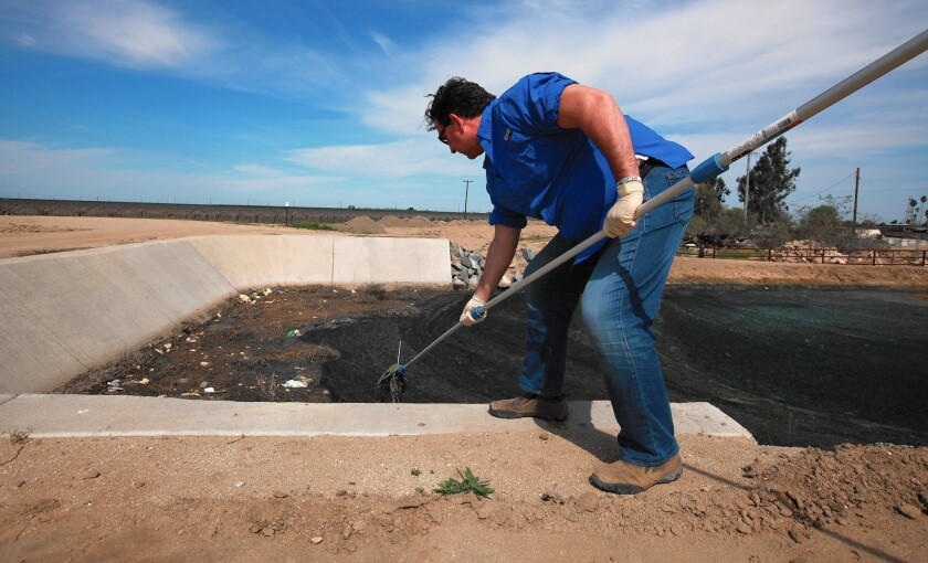Scott Smith of Water Defense conducts a test of water from a canal that carries water from oil production mixed with fresh water.