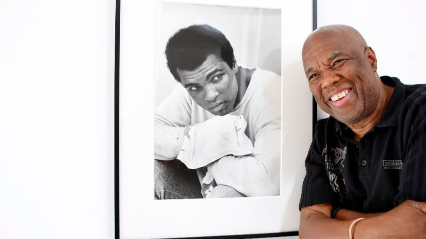 Howard Bingham, the photographer for heavyweight boxing champion Muhammad Ali, poses with one of his portraits at a Hollywood gallery in 2008.