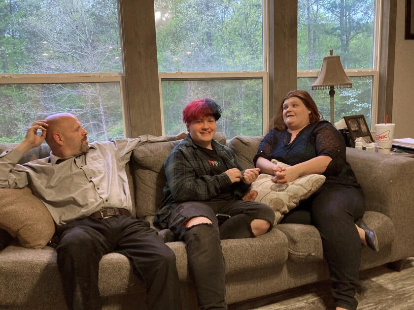 Andrew Bostad, center, talks with his mother, Brandi Evans and stepdad Jimmy Evans at their home in Bauxite, Ark., on Thursday, April 15, 2021. Andrew is one of hundreds of transgender youth in Arkansas who could have their hormone therapy cut off under a new state law banning gender confirming treatments for minors. Opponents have vowed to challenge the ban in court before it takes effect later this year. (AP Photo/Andrew DeMillo)