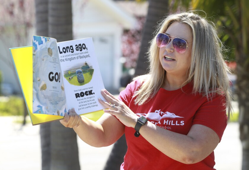 """Library Media Technician for Calavera Hills Elementary School Lindsay Rudy reads """"The Legend of Rock, Paper, Scissors"""" to children while in front of their home on Friday March 27, 2020 in Carlsbad, California."""