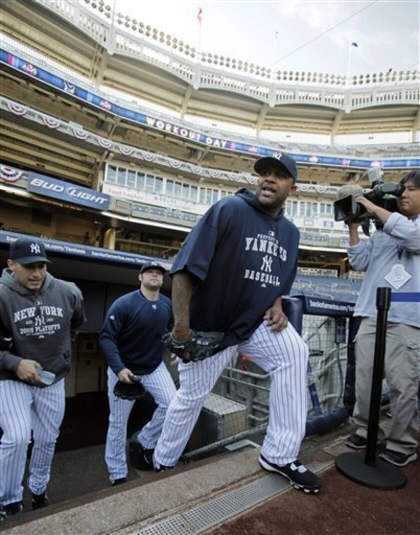 New York Yankees pitchers CC Sabathia, right, Andy Pettitte, left, and Joba Chamberlain emerge from the clubhouse to workout in preparation for their American League division deries baseball game at Yankee Stadium on Tuesday, Oct. 6, 2009 in New York. (AP Photo/Kathy Willens)
