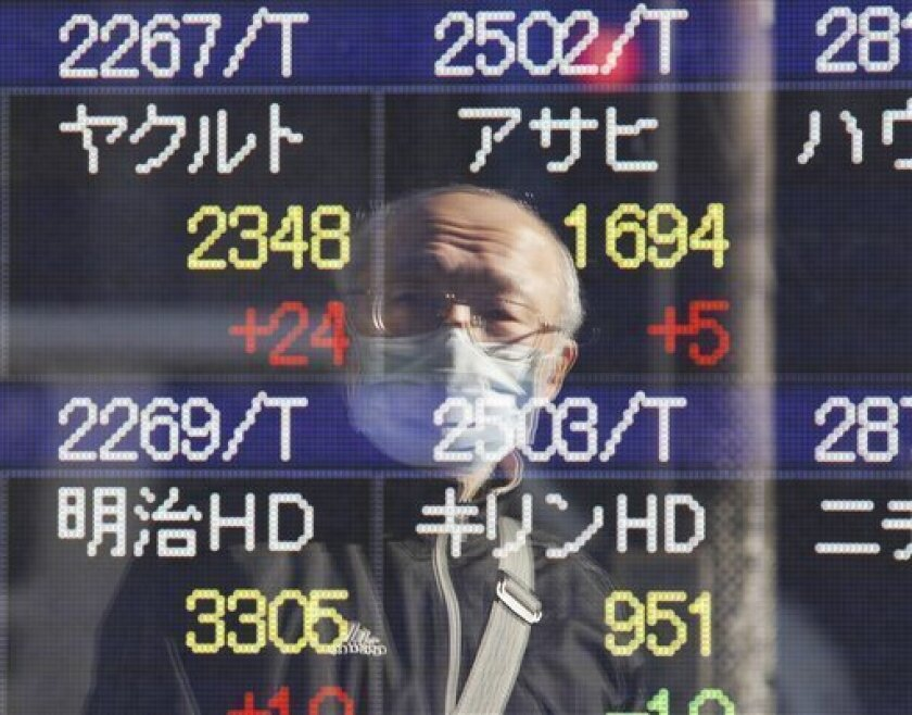A masked man is reflected on an electronic stock board at a securities firm in central Tokyo, Monday, Jan. 30, 2012. Asian stock markets fell Monday, with slower-than-expected growth in the U.S. and uncertainty about a tentative deal to resolve Greece's debt crisis weighing on investor sentiment. (AP Photo/Koji Sasahara)
