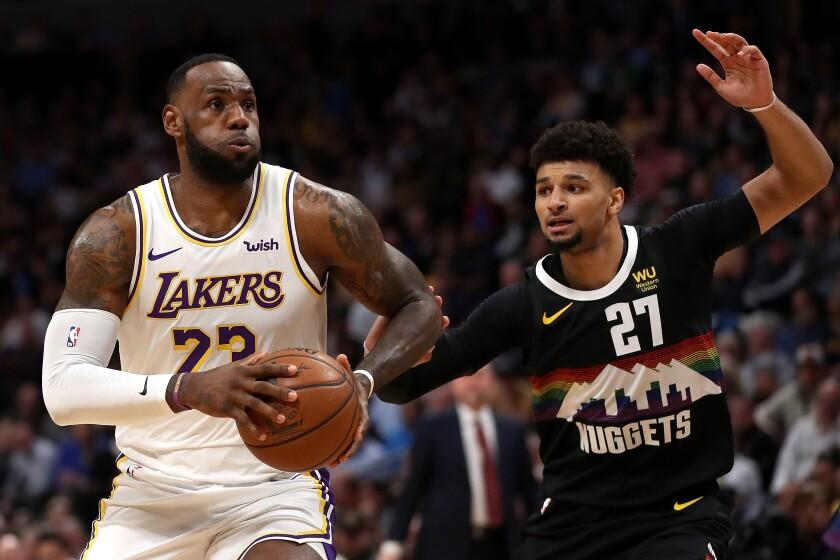 Lebron James (23) de los Lakers conduce contra Jamal Murray (27) de los Denver Nuggets en el primer cuarto del martes en Denver.