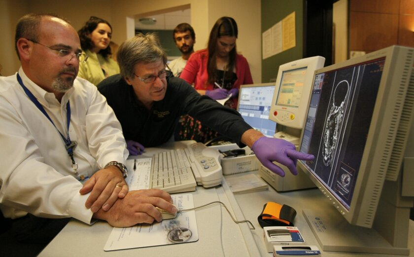 Quinnipiac University anthropologist Ron Beckett (center) leans in for a closer look as Scripps Memorial Hospital La Jolla technician Matt Costa takes a CT scan of a 500-year-old Peruvian mummy Saturday. The San Diego Museum of Man brought in four mummies for scans. Nelvin C. Cepeda / Union-Tribune