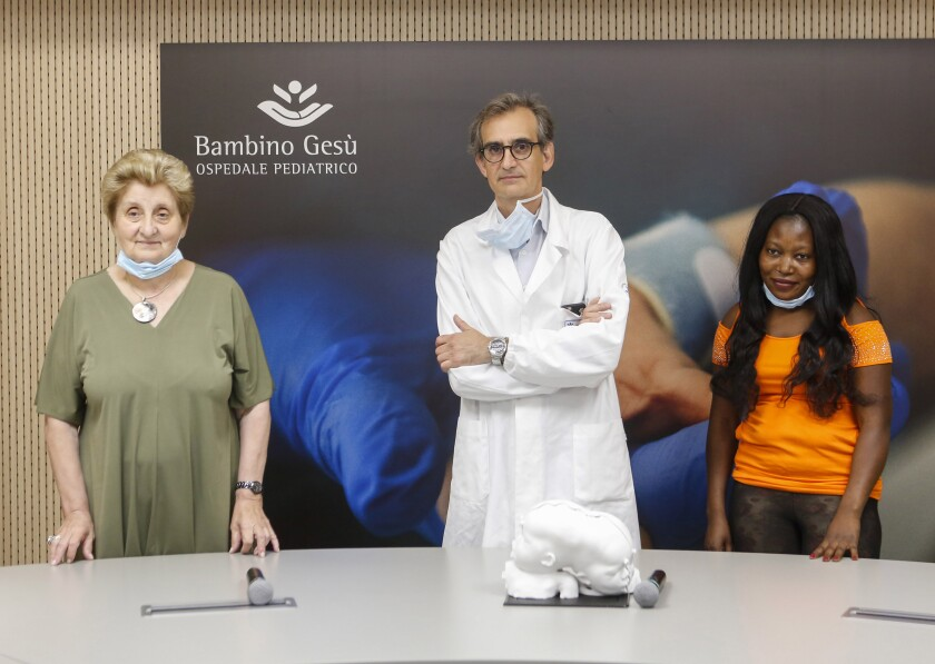 Mariella Enoc, president of the Bambin Gesu' (Baby Jesus) pediatric hospital, left, and Carlo Efisio Marras, head of the hospital's neurosurgery department, center, pose with Ermine, mother of conjoined twins Ervina and Prefina, before a press conference at the Vatican pediatric hospital, in Rome, Tuesday, July 7, 2020. Doctors at the Vatican's pediatric hospital said Tuesday they have successfully separated twins who were conjoined at the back of their skull, an exceedingly rare surgery for an equally rare congenital defect. Twins Ervina and Prefina Bangalo were born June 29, 2018 in the Central African Republic sharing the same skull and critical blood vessels around their brains. (AP Photo/Riccardo De Luca)