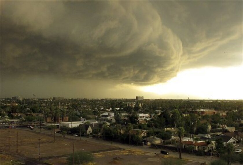 Storm clouds carrying heavy rain move across downtown Phoenix, Tuesday afternoon, Oct. 5, 2010. A series of powerful thunderstorms hit the area with high winds, hail and heavy rain. (AP Photo/Tom Stathis)