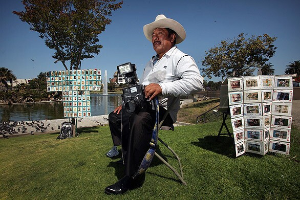 Javier Prado sits in his folding chair waiting for customers at MacArthur Park. Photographers such as Prado, with their old-fashioned Polaroid cameras, have been fixtures in the area for nearly 40 years. See full story