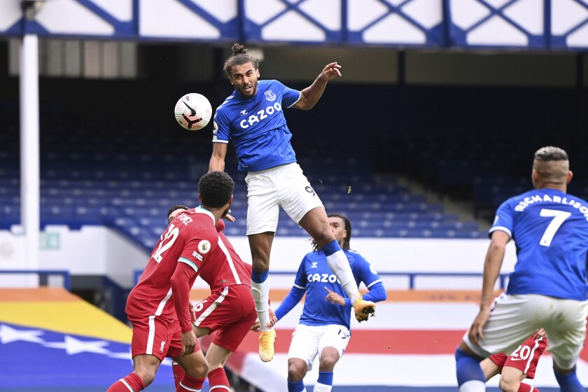 Everton's Dominic Calvert-Lewin, top, scores his side's second goal to make the score 2-2 during the English Premier League soccer match between Everton and Liverpool at Goodison Park stadium, in Liverpool, England, Saturday, Oct. 17, 2020. (Laurence Griffiths/Pool via AP)