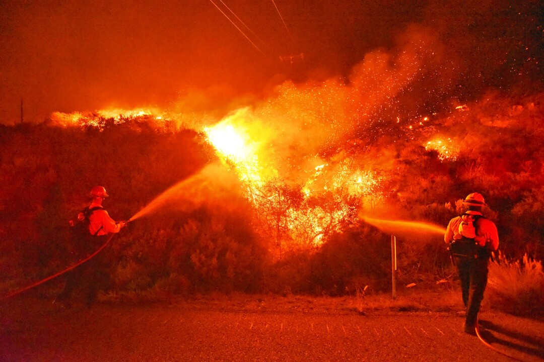 Orange glow illuminates firefighters standing in northbound lanes of the 101 Freeway to spray water on the Alisal fire