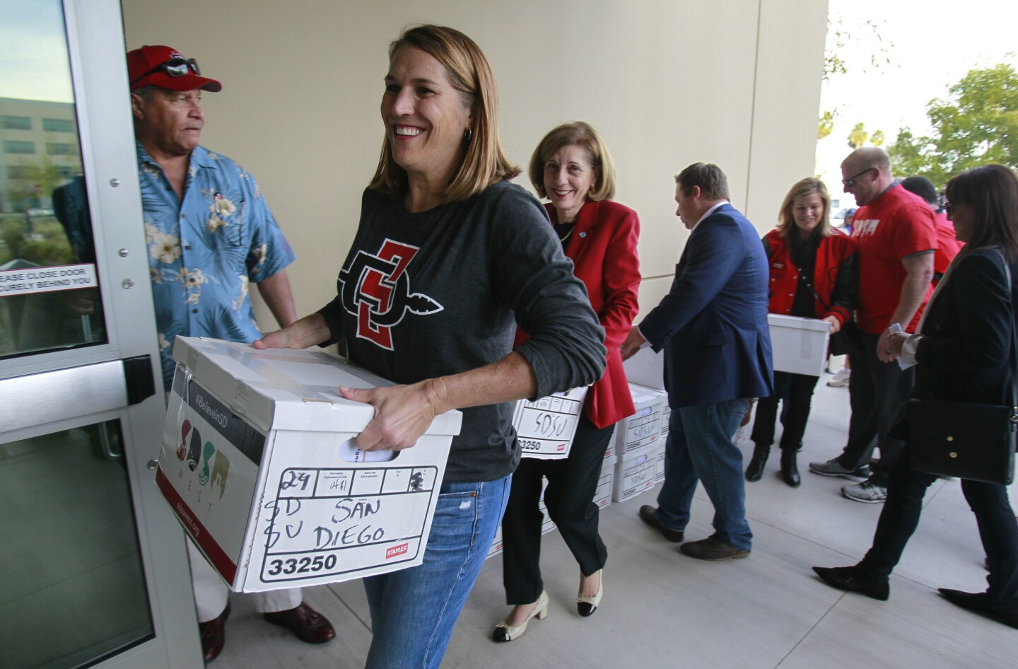 Supporter Kathleen Czech, left, and San Diego City Council member Barbara Bry, center, help carry boxes of the more than 106,000 signatures into the San Diego County Registrar of Voters.