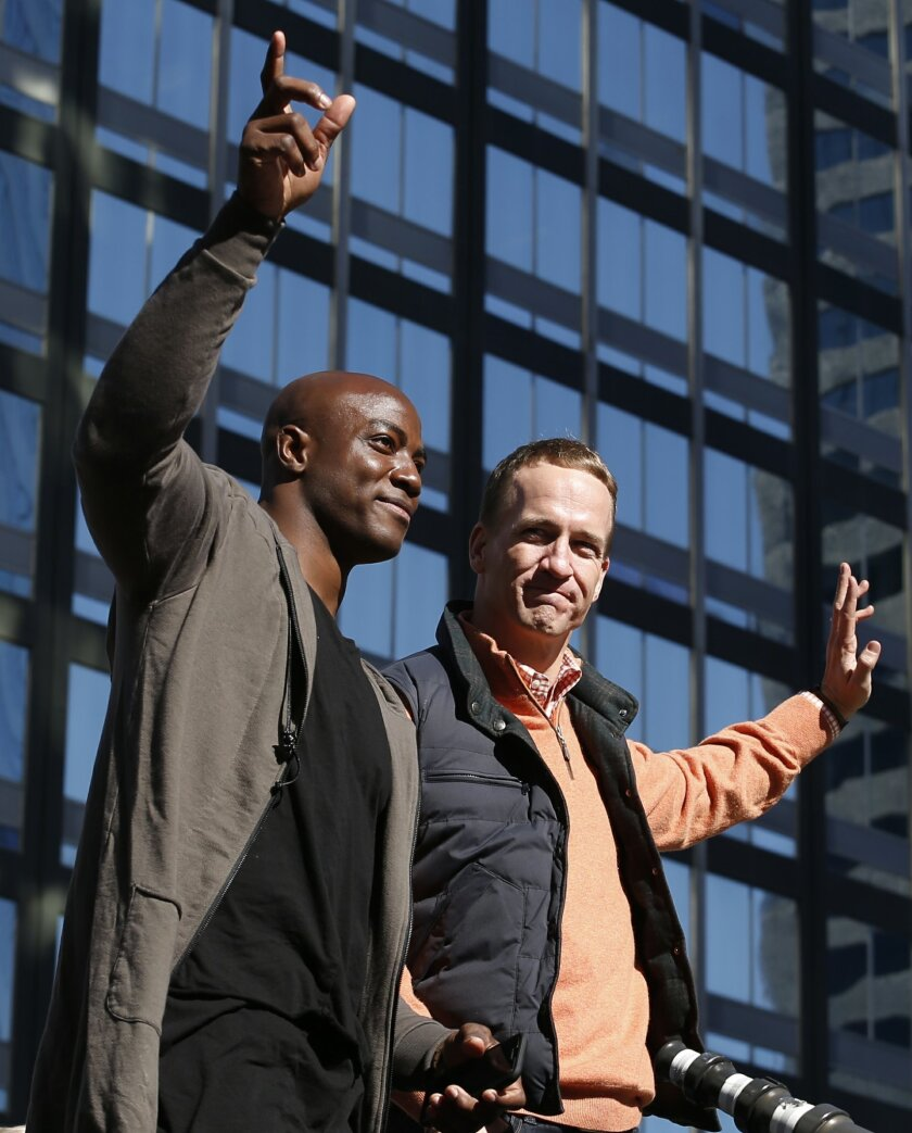 Denver Broncos quarterback Peyton Manning, right, and defensive end DeMarcus Ware wave to fans during a parade for the NFL football Super Bowl champions, Tuesday, Feb. 9, 2016, in Denver. (AP Photo/Jack Dempsey)