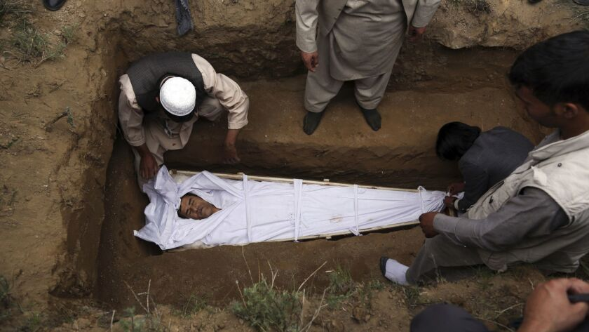 Relatives, colleagues and friends bury the body of AFP chief photographer, Shah Marai, who was kille