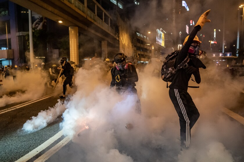 Protesters are enveloped by tear gas Aug. 4 in Hong Kong's Causeway Bay district.