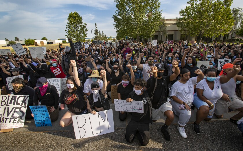Black Lives Matter protesters take a knee.