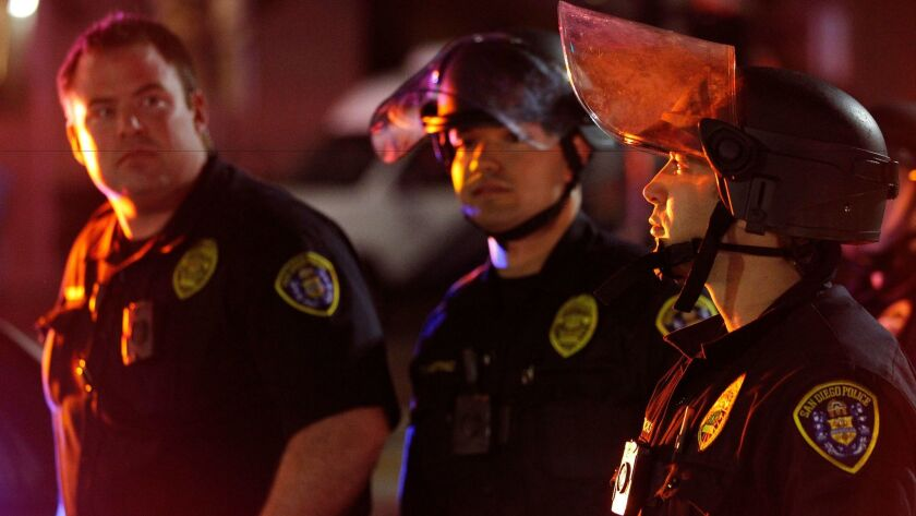 San Diego Police officers, some with riot helmets, watch people protesting president-elect Donald Trump march on Market Street in downtown San Diego on Wednesday.