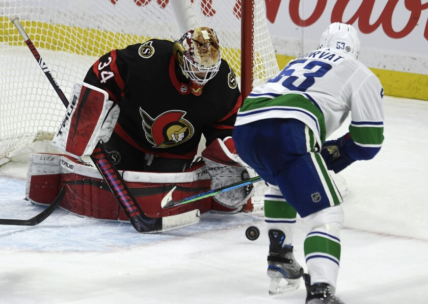 Vancouver Canucks center Bo Horvat tries to control the puck in front of Ottawa Senators' goaltender Joey Daccord during the second period of an NHL hockey game in Ottawa, Ontario, Monday, March 15, 2021. (Adrian Wyld/The Canadian Press via AP)