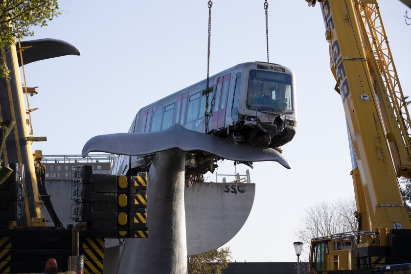 A salvaging crew prepares to attach chains to lift to a metro train carriage of the whale's tail of a sculpture after it rammed through the end of an elevated section of rails with the driver escaping injuries in Spijkenisse, near Rotterdam, Netherlands, Tuesday, Nov. 3, 2020. (AP Photo/Peter Dejong)