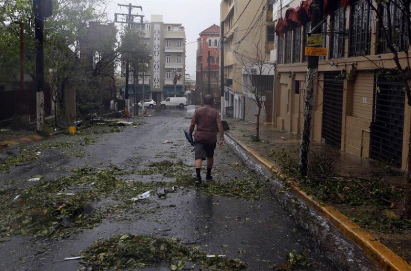 Un hombre camina por una calle llena de arbustos tras el paso del huracán María en el sub-barrio de Miramar de Santurce, en el municipio de San Juan (Puerto Rico). EFE/Archivo