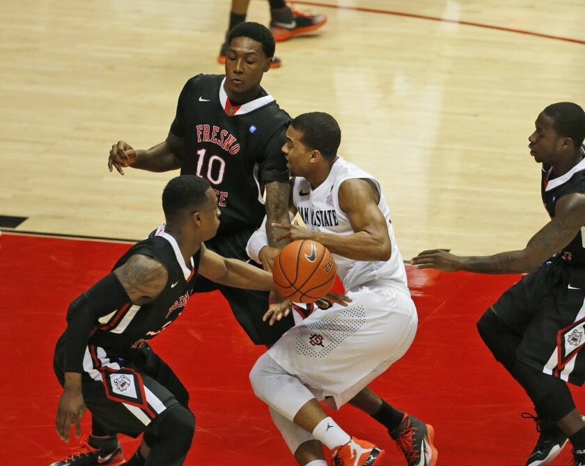 San Diego State guard Aqeel Quinn is stripped of the ball by Fresno State guard Emmanuel Owootoah during the first half of an NCAA college basketball game  Tuesday, Jan. 27, 2015, in San Diego. (AP Photo/Lenny Ignelzi)