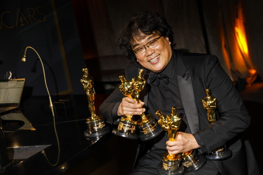 "Bong Joon Ho, winner of directing, writing and the best picture Oscar for ""Parasite"" cradles multiple trophies at the Governors Ball after the Academy Awards."