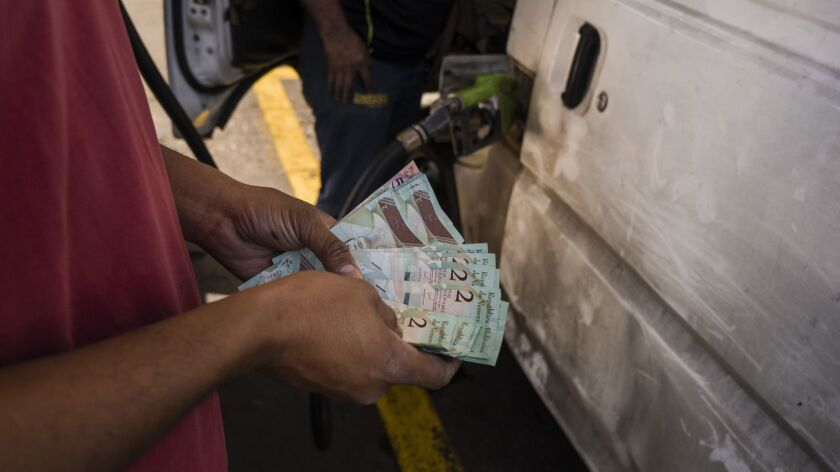 A Caracas gas station worker gives change to a customer.