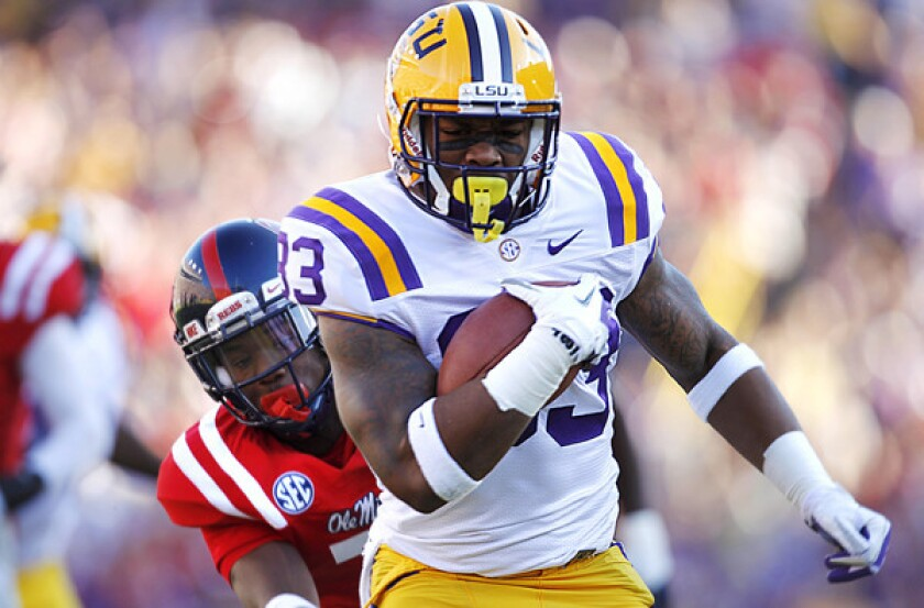 LSU running back Jeremy Hill gets past Mississippi defensive back Trae Elston for a 27-yard touchdown run last season.