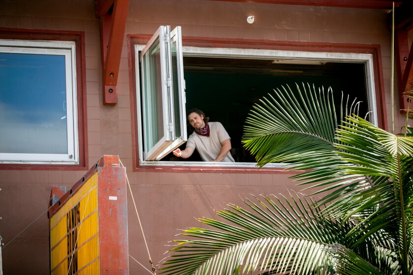 An employee shuts the windows at El Prez shortly after it was ordered shut down ahead of Memorial Day Weekend on May 22, 2020 in San Diego, California.