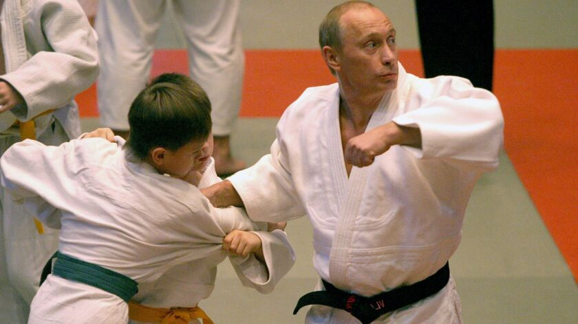Russian President Vladimir Putin demonstrating his judo skills on a young student during his visit to a sports school in St. Petersburg on December 24, 2005.