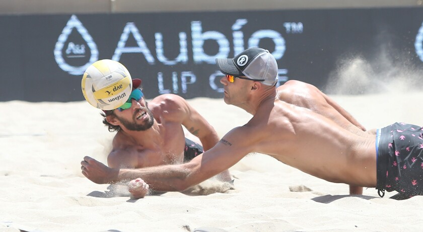 Nick Lucina, left, and Phil Dalhausser, nearly collide as they dig a short shot during the Huntington Beach Open in May.