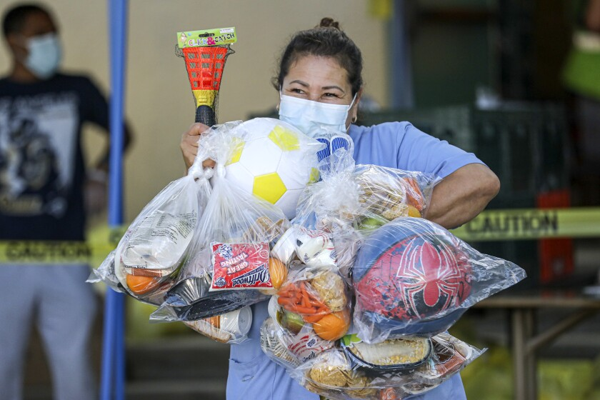 Beatrice Lopez walks out with sports items and meal bags distributed by LA84 Foundation and LAUSD at Grab and Go center at Thomas Alva Edison School on Wednesday in Los Angeles.