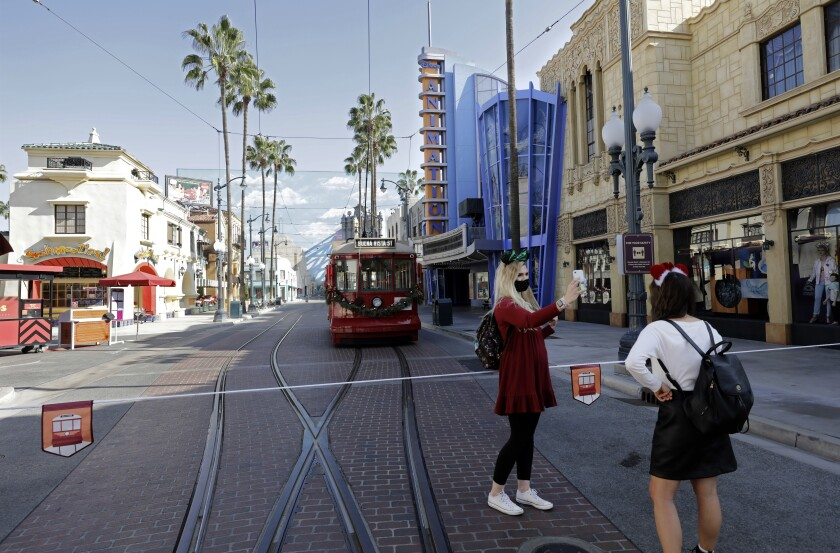 Visitors take pictures in front of a tram at the Disney California Adventure.