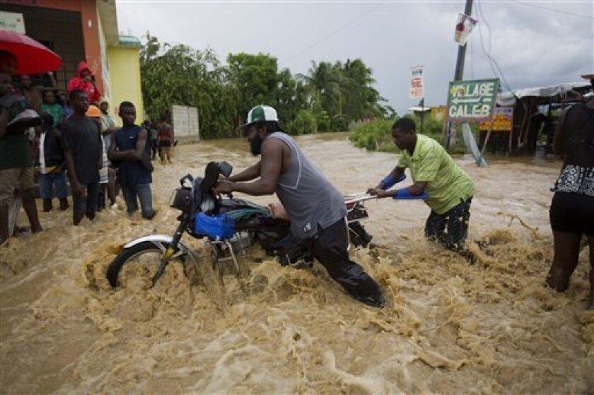 Dos hombres empujan una moto por una calle inundada por un río cercano, desbordado por las fuertes lluvias del huracán Matthew, en Leogane, Haití, el miércoles 5 de octubre de 2016. ( AP Foto/Dieu Nalio Chery)