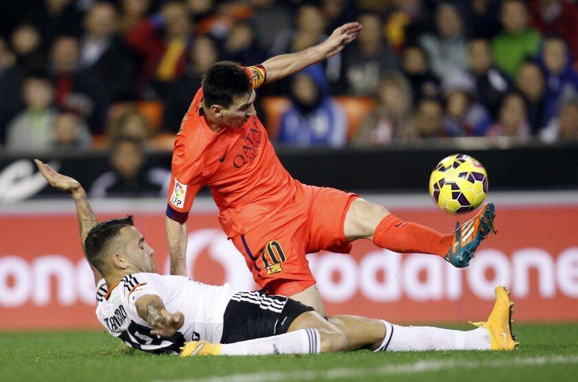 Barcelona's Lionel Messi, from Argentina, top, duels for the ball with Valencia's Otamendi during a Spanish La Liga soccer match at the Mestalla stadium in Valencia, Spain, on Sunday, Nov. 30, 2014.(AP Photo/Alberto Saiz)