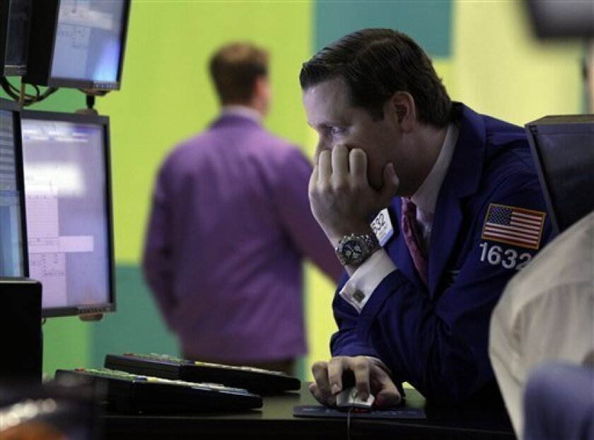 In this July 31, 2012 photo, specialist Gregg Maloney works at his post on the floor of the New York Stock Exchange. The market has had four straight losing days going into Friday, Aug. 3, 2012. (AP Photo/Richard Drew)