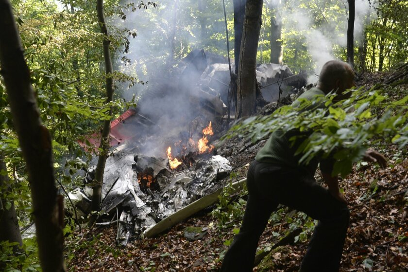 The burning debries of a light aircraft photographed near the village of Cerveny Kamen, Slovakia Thursday, Aug. 20, 2015.Two planes carrying dozens of parachutists collided in midair over western Slovakia, killing several people, officials said. Slovak media reported more than a dozen other parachutists missing and an aviation official said some reportedly survived by jumping out with their parachutes. ( Radovan Stoklasa /TASR via AP)
